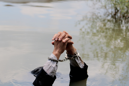 Businessman handcuffed by drowning.