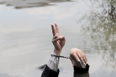 Businessmen put their hands up and he was holding two fingers in the river. Reklamní fotografie