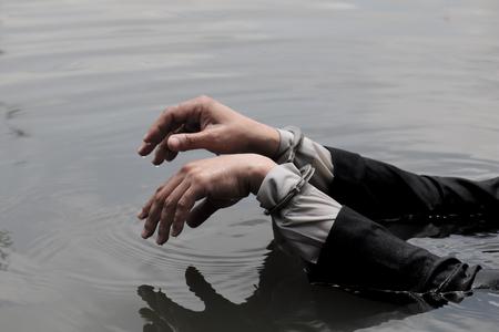 Hand of a businessman handcuffed over water. Reklamní fotografie