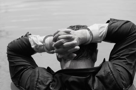 criminal: Businessmen are caught in the water with handcuffs and hands are on the head.Black & White color Stock Photo