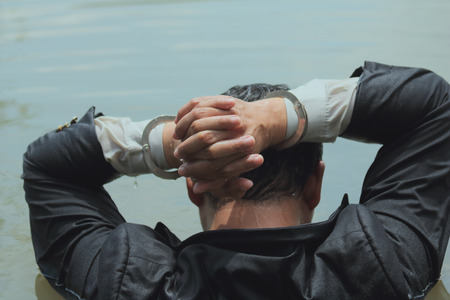 Businessmen are caught in the water with handcuffs and hands are on the head.