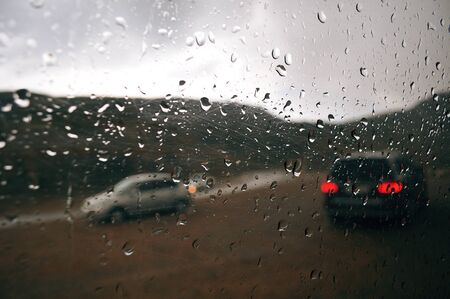 Gray raindrops on the car window on a cloudy day. Outside the window of the car vague silhouettes of passing cars