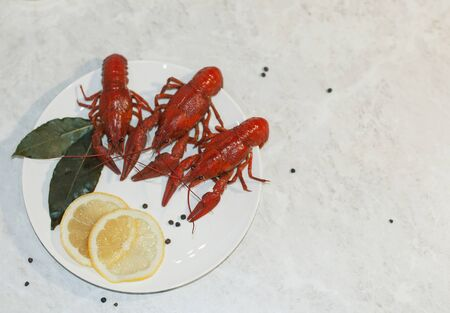 Appetizing plate with three red boiled crayfish, lemon slices and pepper on a marble white table