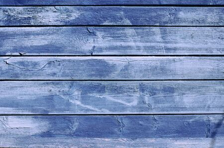 The background of the old painted in blue boards, which peels from the sun and wind paint Фото со стока
