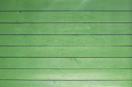 The background of the old painted green boards that are on the wall of the house