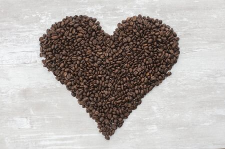 A large brown heart of natural grain coffee lies on the table
