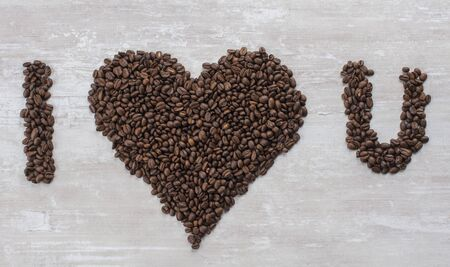 Large brown heart of natural grain coffee lies on the table in the form of the inscription I love you Imagens