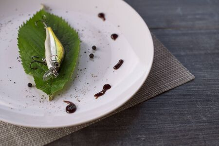 Colored fish bait with sharp fishing hooks lies on a white plate on a wooden table