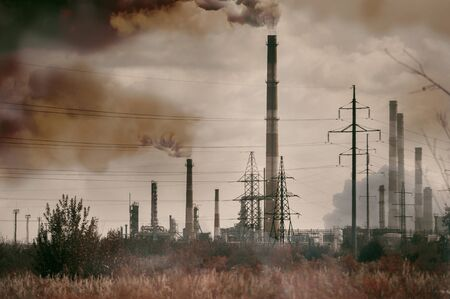view of the refinery with high striped pipes on a background of black smoke. Environmental disaster