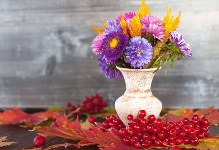 Bright autumn purple and yellow flowers in a vase stand on the table in dry red autumn maple leaves and red viburnum berries on a wooden table Stock fotó