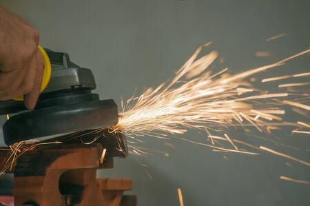 Worker in a workshop grinder processes metal, from which hot bright sparks fly in different directions