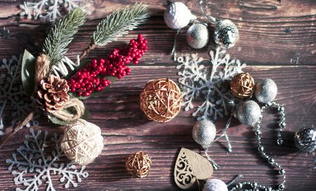 Christmas background of Christmas toys, spruce twigs, snowflakes, stars, rattan balls and tinsel on a wooden brown table Фото со стока