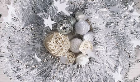 Christmas background from silver shiny tinsel, which lies on a whitened wooden table in the form of a nest, inside the tinsel are New Years white toys and rattan balls
