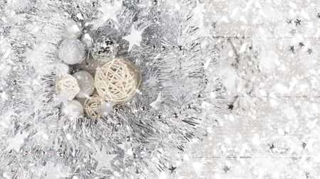Christmas background made of silver tinsel in the form of a wreath that lies on a whitened wooden table next to New Years white toys, white tinsel, snowflakes and rattan balls under the falling snow