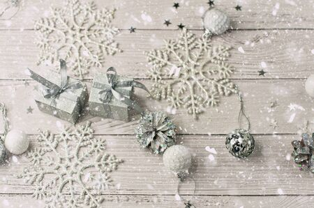 Background for New Year's greetings on a whitened wooden light background with festive silver tinsel, pine natural cones, toys, snowflakes and asterisks and gifts in packing