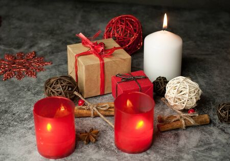 Red and white festive candles burn with a yellow flame on the table among gifts in craft paper, rattan balls, cinnamon sticks and anise stars