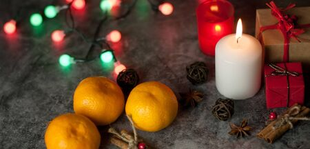 Festive background on which a white candle burns on a table among gifts in craft paper, rattan balls, spruce wreath, tangerines, cinnamon sticks on the background of a multi-colored Christmas garland and red tinsel with snowflakes Stock Photo
