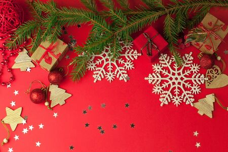 Christmas festive red background with a fir branch, under which are gifts in craft paper among Christmas decorations, toys and snowflakes