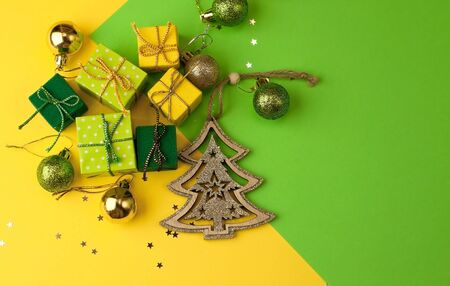 Christmas graphic multi-colored background  from yellow, green and blue paper with a geometric pattern, with gifts and Christmas toys in a package with a scourge Foto de archivo