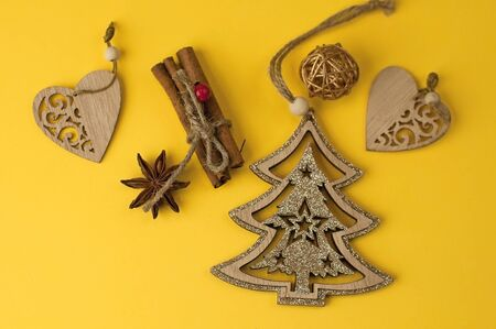 Christmas background from yellow paper with place for text, with wooden decorative Christmas tree decorations, stars. Foto de archivo