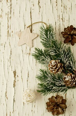Retro Christmas background on old cracked wooden background with peeling white paint with gifts in craft paper, a scourge and wooden Christmas tree decorations