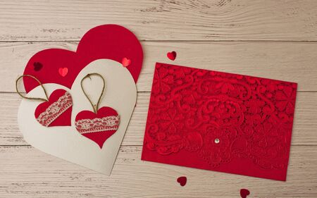 Holiday background for Valentines Day on a white wooden background with carved hearts with place for text, with a bright red carved postcard and rattan balls