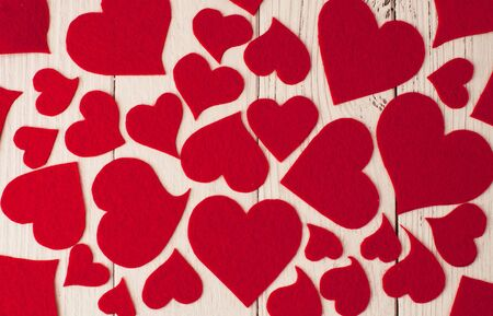 Holiday  background for Valentines Day on a white wooden background which consists of red hearts.