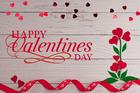 Holiday background for Valentines Day on a white wooden background with felt carved hearts with place for text.