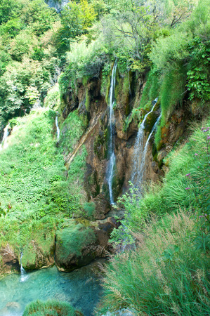 azure: High waterfall among green foliage. Water falling from brown rocks into a clear turquoise pond. Plitvice lakes national park, Croatia Stock Photo
