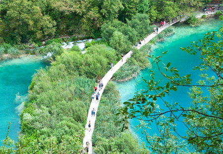 Tourists walking along a hiking path among two ponds with turquoise water. View from above. Plitvice lakes national park, Croatia Editorial