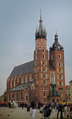 View on the St. Marys Basilica in the center of Krakow and a square crowded with blurred figures of tourists, pigeons. Warm pastel colors. Cloudy day in spring
