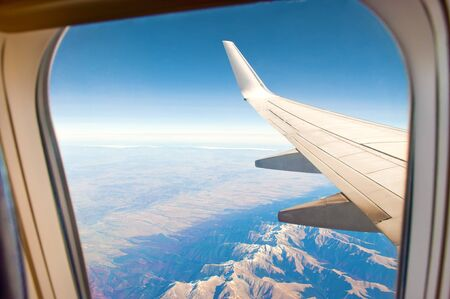 White airplane wing shor from a window. Aerial view of majestic mountain range with snow-capped peaks, green and red forest, fields, blue sky and horizon. Sunny cloudless autumn day