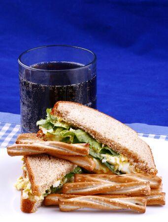 Egg salad sandwich with pretzels and drink