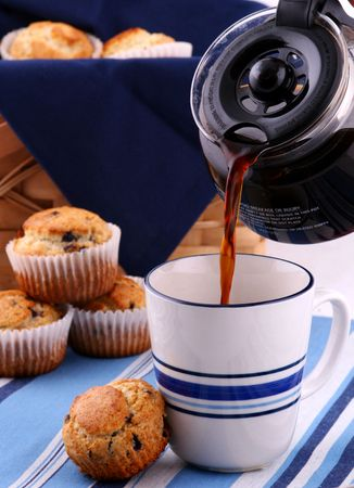 coffee being poured into a mug with blueberry muffins in the background