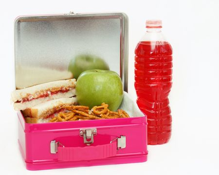 jelly sandwich: Pink metal lunchbox filled with peanut butter and jelly sandwich, pretzels and an apple with a drink to the side on an isolated white background