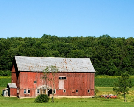 old barn, with metal roof, in the countryside on a sunny day with a clear blue sky photo