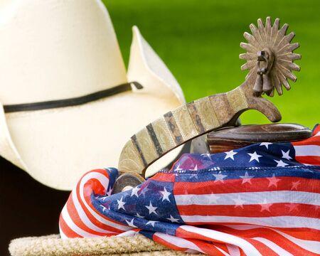 cappello cowboy: Sperone, corno di sella, cappello da cowboy, corda e patriottica materiale con erba verde sullo sfondo, di fuori, in una giornata di sole
