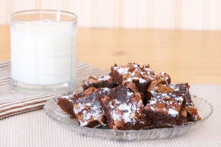 Brownies on a plate covered with caramel and powdered sugar with a glass of milk in the background
