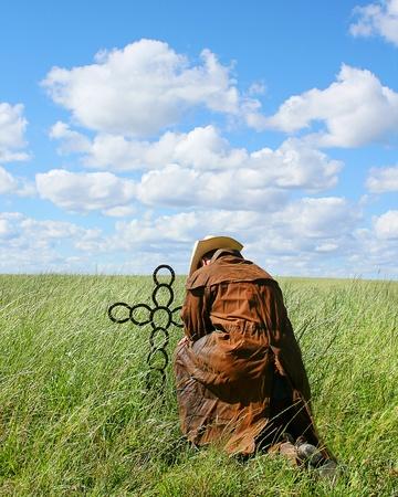 cowboy praying at a metal cross on sunny summer day photo