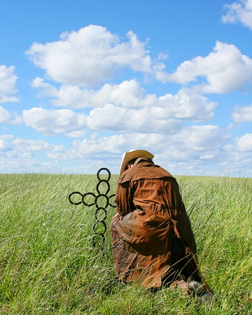 cowboy praying at a metal cross on sunny summer day Stock Photo