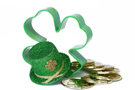 Shamrock hat decoration with shamrock shaped cookie cutter and gold coins isolated on white background photo
