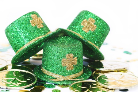 three green glitter hats with gold shamrocks on them wiht gold coins and confetti for St. Patricks Day