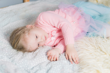 Little girl in a pink sweater falls asleep on the bed. Imagens
