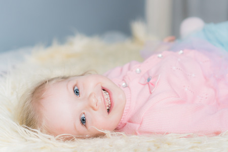 Little girl in a pink jacket lying on the bed and smiling.