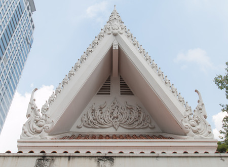pediment: Pediment Thai temple in modern city. Stock Photo