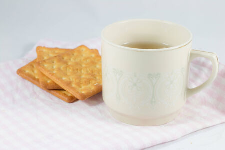 A cup of tea with crakers.