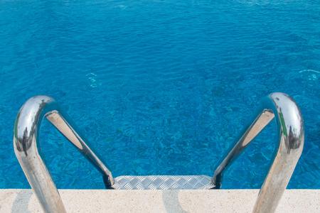 metallic stairs: Metallic stairs in outdoor swimming pool Stock Photo