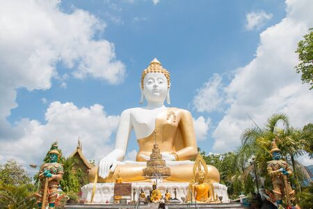 extreme angle: Sitting Buddha Statue at WAT PHRATHAT DOI KHAM.Chiang mai, Thailand.Made by donation