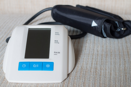 medical device: Digital blood pressure on table in a home with soft focus. Stock Photo