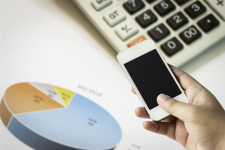 finance background: Hand on smartphone with finance background. Stock Photo